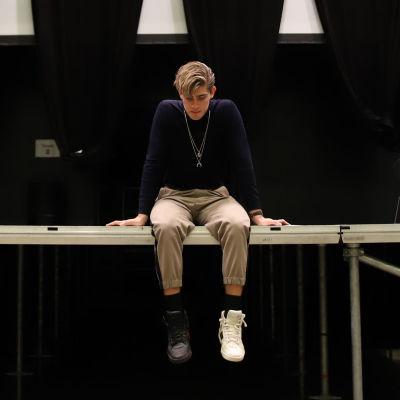 Robin Packalen istumassa tyhjällä lavalla Logomossa joulukuussa 2020. Keskitetty lähikuva.