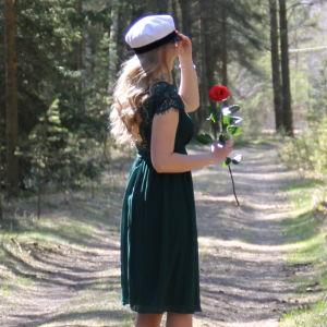 Kvinna med studentmössa som står i en skog.