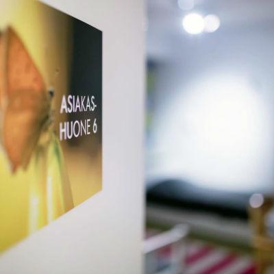 """En skylt med bilden på en fjäril med texten """"kundrum 6"""". I bakgrunden ses ett rum med flera sängar."""