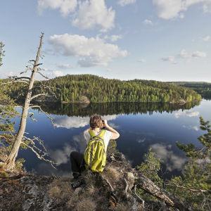 En man sitter på ett berg och tittar mot ett spegelblankt vatten