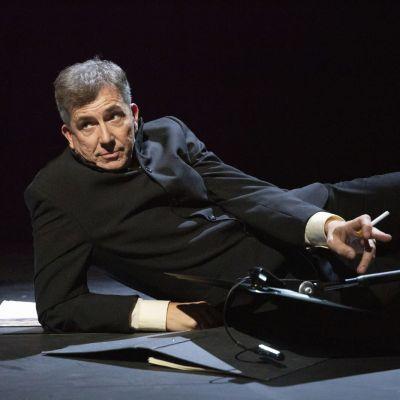 Skådespelaren Joachim Wigelius halvligger på en mörk scen med travar av vita papper omkring sig på golvet.