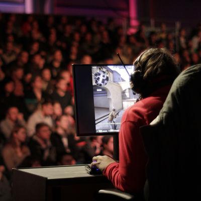 spelare på Assembly där en massa människor sitter i publiken i bakgrunden.