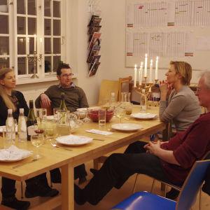 Seurue katetun pöydän ääressä juhlimassa rauhallisesti, kynttelikkö pöydän päässä.