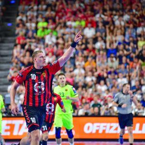 Dainis Kristopans pekar mot publiken.