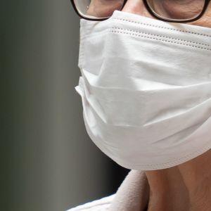 Närbild på en person (kvinna) som använder ett vitt munskydd som täcker både mun och näsa.