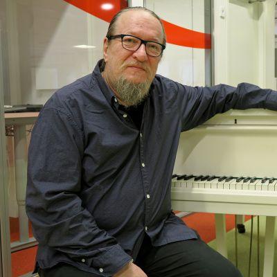 Muusikko Jaakko Löytty istuu flyygelin ääressä