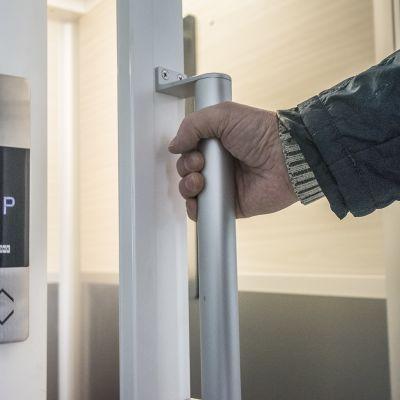 Mies avaa hissin oven.