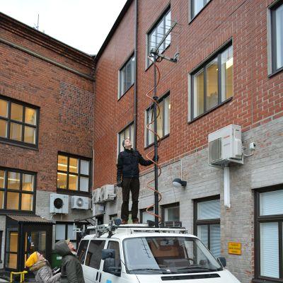 Timo Ruuskanen on kiivennyt Ylermin katolle tarkistamaan antennia, Liisa Leinonen ja Mari Vesanummi katsovat vierestä.
