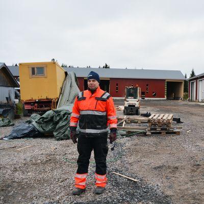 Maanviljelijä Sami Isola rakenteilla olevan hakelämpökeskuksen edessä.