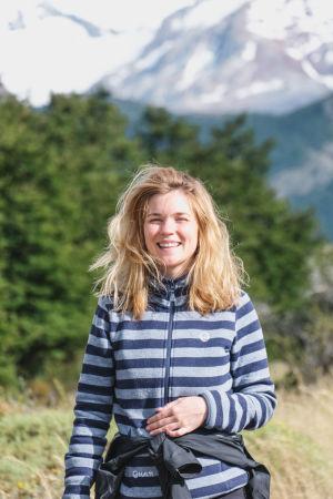 En kvinna iklädd en randig fleecetröja. Hennes blonda hår är rufsigt och hon skrattar stort. I bakgrunden syns träd och berg.