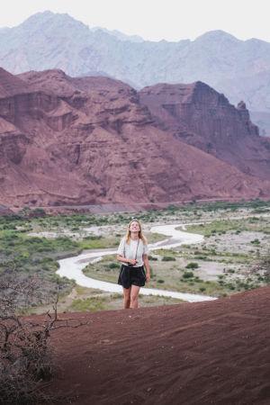 En kvinna iklädd t-skjorta och shorts kommer gående. Hon ler. I bakgrunden syns berg och en flod.