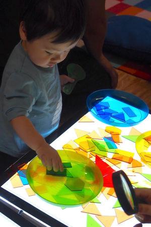 Pojke skapar med färggranna plasttrianglar.