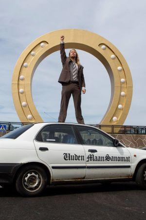 Pitkähiuksinen nuorimies seisoo oikea käsi nyrkkiin kohotettuna auton katolla, taustalla suuri tyylitelty hevosenkenkäveistos.