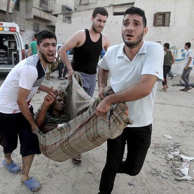 Palestinier för bort en skadad man efter en israelisk attack mot ett torg i Gaza 30.7.2014