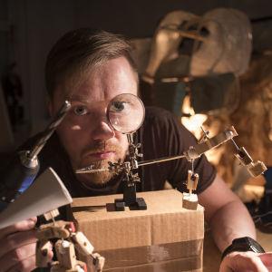 Nukentekijä Aapo Repo tiiraa suurennuslasin läpi työkalua, jolla tehdään nukkeja.