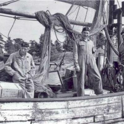 En konfiskerad trålare fylld med sprit i Sondarö år 1955. Sjöbevakare från sjöbevakningsstationen i Risholma. På bild från höger: Olavi Hotanen, Jalo Haapala, Pentti Hurri.