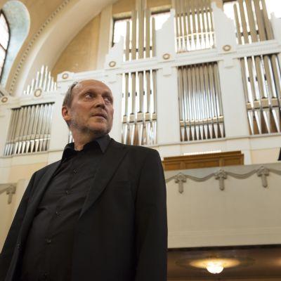 Peter Hilli framför orgelfasaden i Berghälls kyrka