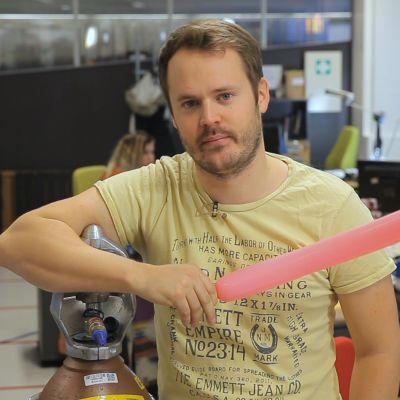Dan står med en avlång ballong i handen