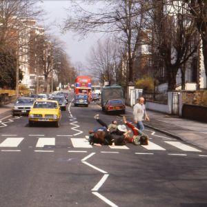 Neljä ihmistä makaa sikinsokin toistensa päällä suojatiellä Britanniassa, muusikko Juice Leskinen kävelee ohitse.