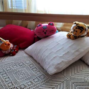 leluja sängyssä päiväpeiton päälle aseteltuna