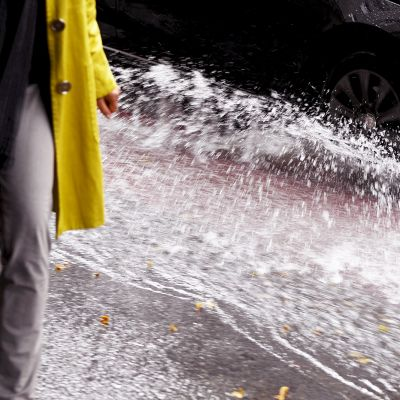 Auton renkaista roiskuaa vettä jalankulkujan päälle.