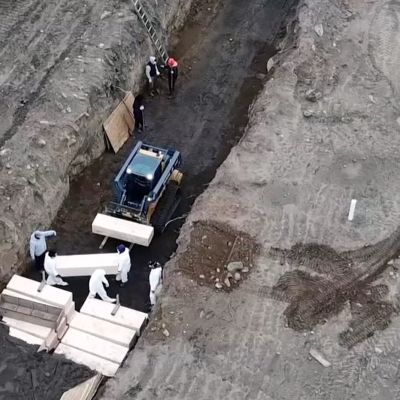 Lautaisia arkkuja kasataan joukkohautaan New Yorkissa.