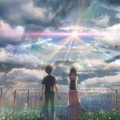 En pojke och en flicka står på ett tak och ser på en färgsprakande himmel där solstrålarna precis bryter fram.