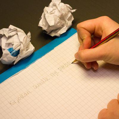 Nuori kirjoittaa lyijykynällä ruutupaperille tekstiä.