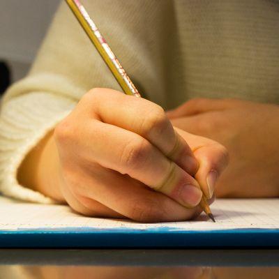 Nuori kirjoitaa paperille lyijykynällä tekstiä. kirjoittaminen kirje käsiala lyijykynä oppiminen lehtiö koulu paperi kello
