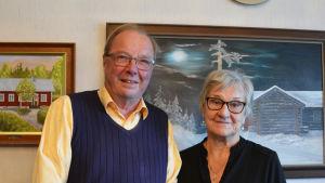 En äldre man och en äldre kvinna står framför en vägg prydd med oljemålningar.