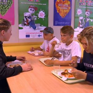 Fyra pojkar sitter i en skolmatsal och äter.