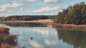 Bild på vatten fotograferad i Lielax i Pargas. I bakgrunden syns båt och åker.
