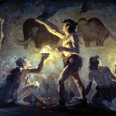 Förhistoriska människor i en grotta, målande på väggen.