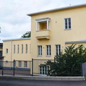 En stor gul byggnad med flera våningar ligger invid en gata.