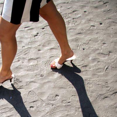 Naiset korkokengissä kävelee hiekalla.