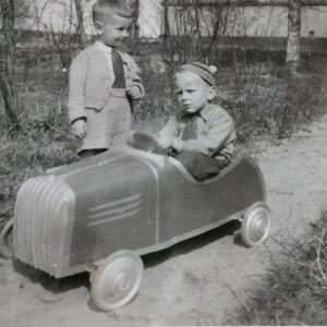 Kaksi pientä poikaa ja polkuauto 1950-luvulla.