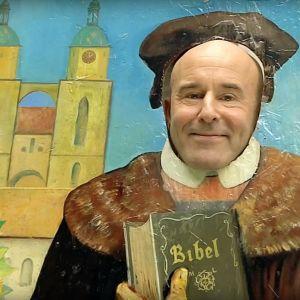 Mark Levengoods ansikte bakom en pappfigur av Marthin Luther.