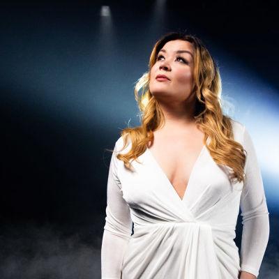 UMK-finalisti Catharina Zühlke poseeraa valkoisessa mekossa tummansinertävän taustan edessä. Hänen takaansa tulee kirkas vaalea valokeila.