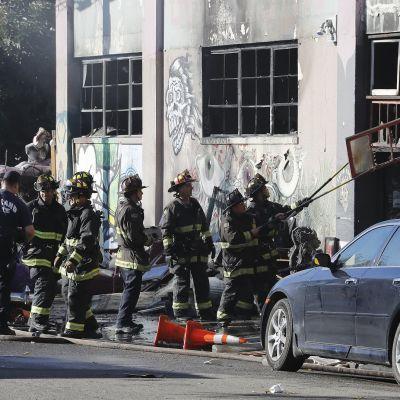 Palomiehet raivasivat tulipalossa tuhoutunutta varastoa joulukuussa 2016.