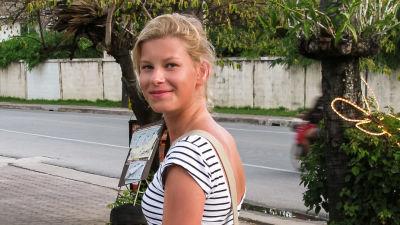 Sara promenerar på trottoaren och vänder sig leende mot kameran.
