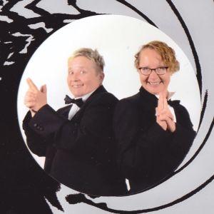 Tutkija Tuula Juvonen kumppaninsa Ritvan kanssa James Bond -elokuvajulisteita mukailevassa kuvassa.