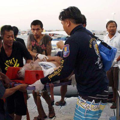 Räddningsarbetare bär en skadad turist.