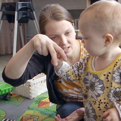 Nainen viittoo vauvalle.