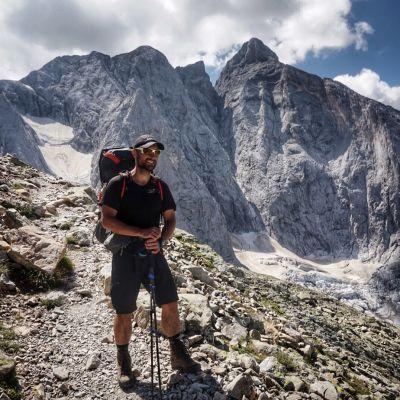 Peter Jofs står uppe i bergen och poserar framför kameran. Iförd vandringsutrustning.