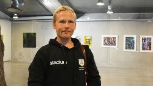 En ung man i svart luvtröja står inne i Konstfabriken i Borgå. Bakom honom syns grå väggar och tavlor.