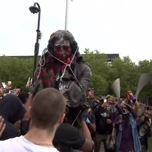 En folkmassa välter en staty