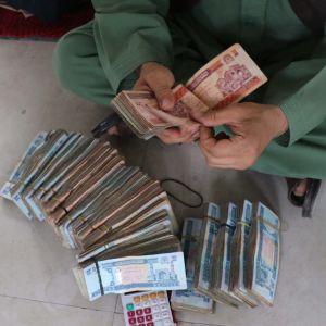 Ihminen istuu lattialla rahanippuja edessään