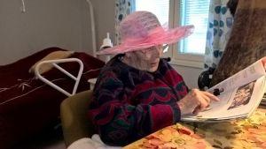 En gammal dam med en vacker hatt på.