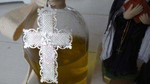 En staty av en nunna vid en glasflaska med olja.