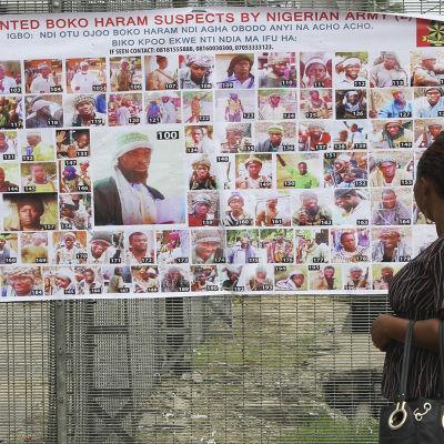 En kvinna tittar på en affisch med bilder av efterlysta misstänkte Boko Haram-anhängare.